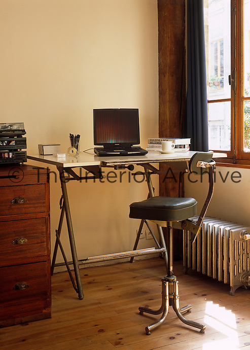A corner of the living space has been converted into a small home office/study with a retro desk and chair