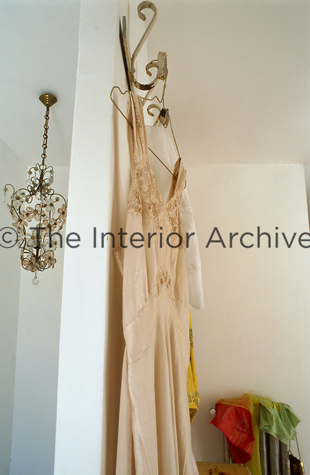 A vintage silk evening dress hangs from an old hook on a wall of the living room