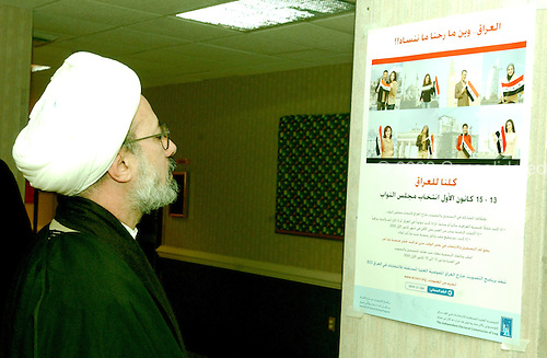 McLean, VA - December 13, 2005 -- Imam Fadhel Al Sahlani, who emigrated to Jamaica, Queens, New York from Basra, Iraq, looks at an election poster hanging inside the polling place for the Iraqi election in McLean, Virginia on December 13, 2005.  Imam Al Sahlani is affiliated with the Al Khoei Benevolent Foundation in New York, New York..Credit: Ron Sachs / CNP.(RESTRICTION: NO New York or New Jersey Newspapers or newspapers within a 75 mile radius of New York City)