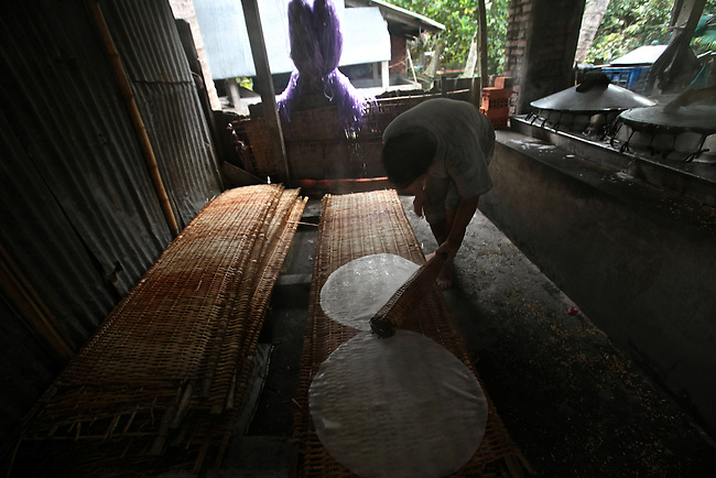 A man spreads a freshly made rice noodle sheet on a mat to dry at a small factory in the Mekong Delta, south of Can Tho, Vietnam. Sept. 30, 2011.