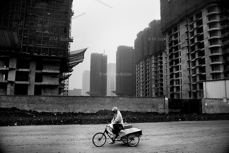 A worker pedals a bike past new high-rise apartment construction in Nanjing, Jiangsu, China.