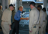 New Orleans, Louisiana - September 11, 2005 -  United States President George W. Bush pauses to shake the hand of the Navy personnel standing quarterdeck watches before departing the amphibious assault ship USS Iwo Jima (LHD 7). President Bush visited New Orleans and Iwo Jima to observe first hand the results of the rescue and recovery missions carried out by the military. Iwo Jima is currently pier side in New Orleans, assisting in Joint Task Force Katrina hurricane relief efforts to bring much needed supplies and help to Gulf Coast region. The Navy's involvement in the humanitarian assistance operations is being led by the Federal Emergency Management Agency (FEMA), in conjunction with the Department of Defense. <br /> Credit: Christian Knoell - U.S. Navy via CNP
