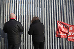 Two spectators looking through iron gates outside the Alexandra Stadium on Gresty Road, Crewe, the home of Crewe Alexandra before their home game against Leyton Orient in the SkyBet League One. The match was won by the visitors from London by 2-1 with two goals on debut by Chris Dagnall, sending Orient to the top of the league. The match was watched by 4830 spectators.