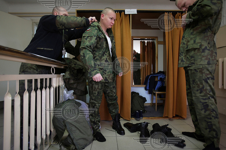 Conscript Piotr Piotrkowicz puts on his uniform for the first time. This year's class of drafted recruits is the final one after 90 years of compulsory military service, as Poland's army turns professional in 2009.