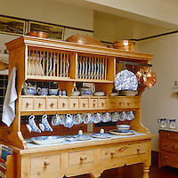 A large dresser displaying antique copper pans and traditional blue and white china stands in the kitchen