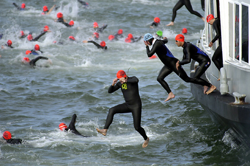 "PICO VAN HOUTRYVE/Examiner 6.10.01 news: Triatheletes in wet suits and swim caps jump from the port side of the California Hornblower at the start of the 21st annual ""Escape from Alcatraz"" triathalon in the San Francisco Bay near Alcatraz Island, Sunday, June 10, 2001."