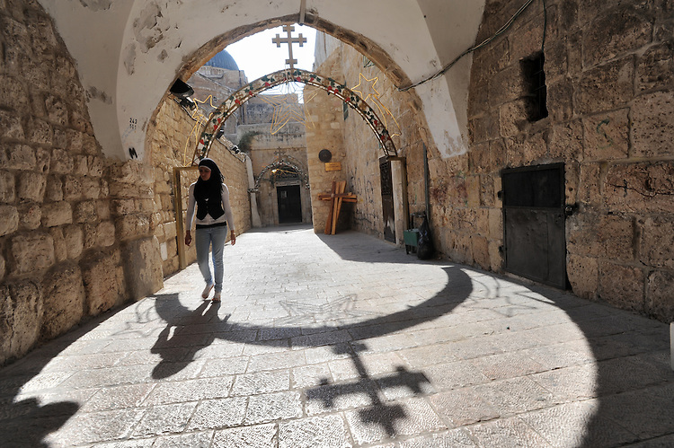 A woman passes by the ninth station of Via Dolorosa, a street within Jerusalem's old city, which is believed to be the path that Jesus Christ walked carrying his cross, on his way to crucifixion.<br />
