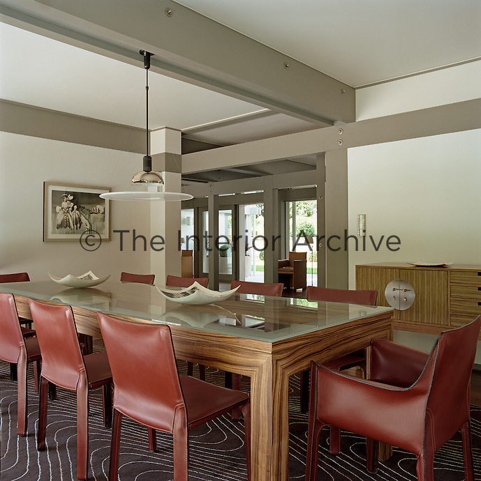 Chairs upholstered in red leather surround the glass-topped wooden dining table in this contemporary dining room