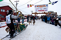 The first ever Jamaican musher Newton Marshall runs down the finish chute in Nome during the 2010 Iditarod
