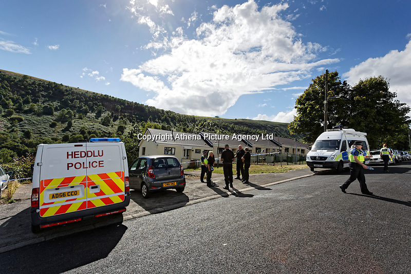 Pictured: Police officers outside the house where the body of David Gaut was discovered in New Tredegar, Wales, UK. Wednesday 08 August 2018<br /> Re: Three men have been arrested after a man was found dead at a house in New Tredegar, Wales, UK.<br /> David Gaut, 54, was found in Long Row, in the Elliots Town area of New Tredegar, on Saturday, August 4.<br /> Two two-storey terraced homes, owned by Caerphilly council, have been cordoned off and police officers are patrolling the area. <br /> David Gaut was jailed for life in July 1985 when he was 21 years old, for the murder and torture of17-month old Chi Ming Shek