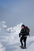 Appalachian Trail - A hiker photographing on the summit of Carter Dome in winter conditions. Located in the White Mountains, New Hampshire USA