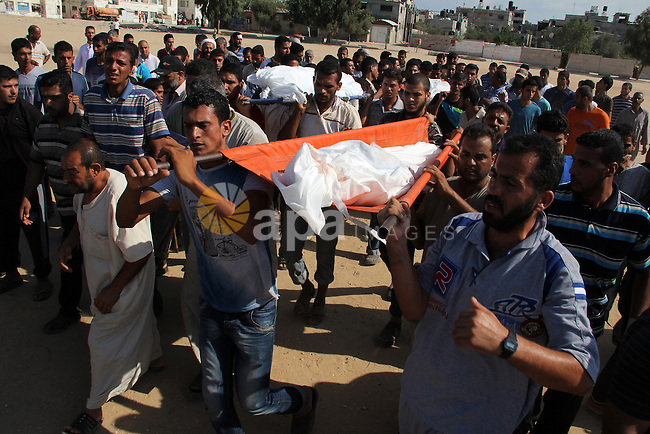 Palestinian mourners carry the body of a Palestinian from Abu Hadaf family, whom medics said was killed along with two other family members by an Israeli air strike, during their funeral in Khan Younis in the southern Gaza Strip August 9, 2014. Israel launched more than 20 aerial attacks in Gaza early on Saturday and militants fired several rockets at Israel in a second day of violence since a failure to extend an Egyptian-mediated truce that halted a monthlong war earlier this week. The Israeli military said that since midnight it had attacked more than 20 sites in the coastal enclave where Hamas Islamists are dominant, without specifying the targets. Medical officials in Gaza said two Palestinians were killed when their motorcycle was bombed and the bodies of three others were found beneath the rubble of one of three bombed mosques. The air strikes which lasted through the night also bombed three houses, and fighter planes also strafed open areas, medical officials said. Photo by Abed Rahim Khatib
