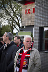 Fans gathering outside the main stand at Broadhurst Park, Manchester, the new home of FC United of Manchester before the club's match against Benfica, champions of Portugal, which marked the official opening of their new stadium. FC United Manchester were formed in 2005 by fans disillusioned by the takeover of Manchester United by the Glazer family from America. The club gained several promotions and played in National League North in the 2015-16 season, but lost this match 1-0.
