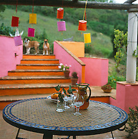 A jug of Pimms and a mosaic table on a summer terrace, with paper lanterns hanging from the arbour reflecting the colours of the walls and steps beyond