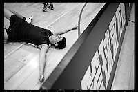 An exhausted player of Tsinghua University Affiliated Middle School basketball team lies on the floor during a training session at Tsinghua University Affiliated Middle School in Beijing, January 2012.