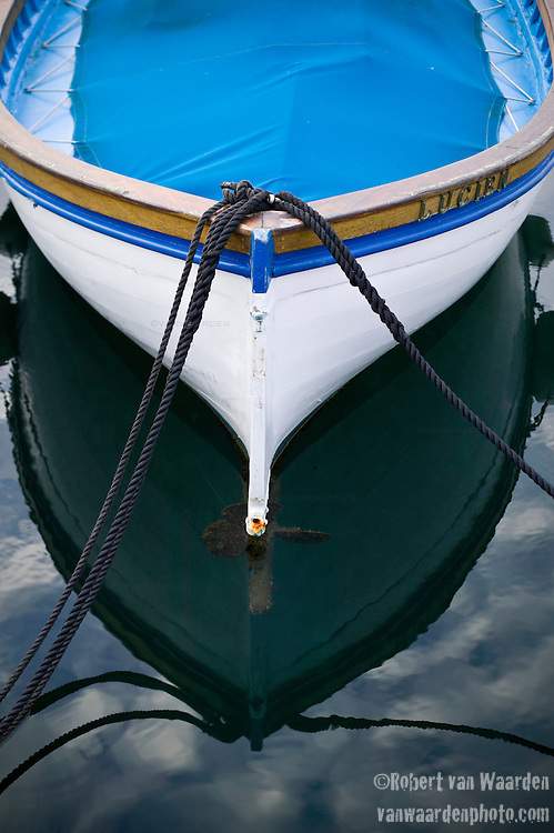 The bow of a boat in the harbour in Cannes, France with the sky reflected in the water.