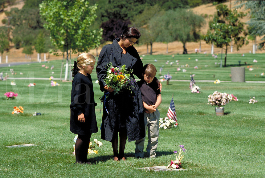 BEREAVED CAUCASIAN MOTHER AND CHILDREN AT GRAVESIDE OF FATHER. GRIEVING FAMILY. NOVATO CALIFORNIA.