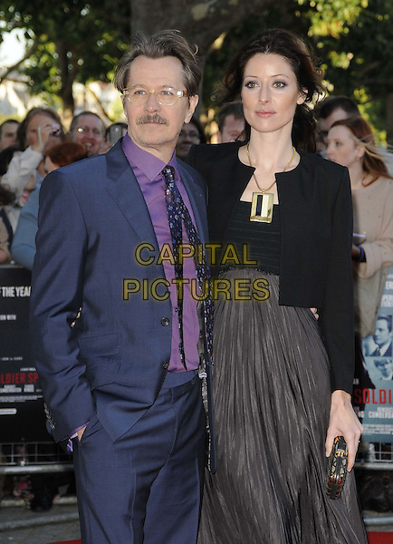 "GARY OLDMAN & ALEXANDRA EDENBOROUGH.The ""Tinker, Tailor, Soldier, Spy"" UK premiere, BFI  Southbank cinema, Belvedere Rd., London, England..September 13th, 2011.half length blue suit pink shirt glasses moustache mustache facia hair hands in pockets black blazer grey gray dress gold necklace .CAP/CAN.©Can Nguyen/Capital Pictures."