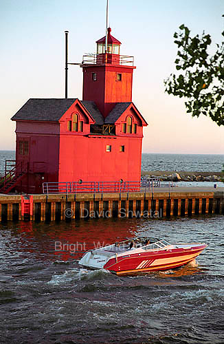 A red pleasure craft glides by the red lighthouse near the Holland Michigan Harbor in the evening