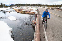 A biker explores the Grand Loop Road during spring biking season in Yellowstone National Park.