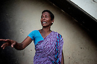 Indra (42 years) crying and explains her poverty stricken situation standing at her open air kitchen. Cuddalore, Tamil Nadu, India.