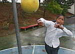 Romani Busby (9) swings a boxers punch at a ball on the playground during recess at MalcolmX elementary school, Hunter point,  San Francisco, California..