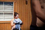 Jacob Hoffman, 20, stands on the porch of the small house he rents in Crystal City, Texas with his brother and their families. His girlfriend, Lori, shields their baby daughter from the sun. Mr. Hoffman recently moved from Oklahoma to work in the oilfields of south Texas. October 2, 1012. Copyright Lance Rosenfield/Prime