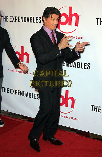 """SYLVESTER STALLONE .Special Screening of """"The Expendables"""" at Planet Hollywood Resort Hotel and Casino, Las Vegas, Nevada, USA,.11th August 2010..full length sly pink purple shirt tie suit black hands gesture side .CAP/ADM/MJT.© MJT/AdMedia/Capital Pictures."""