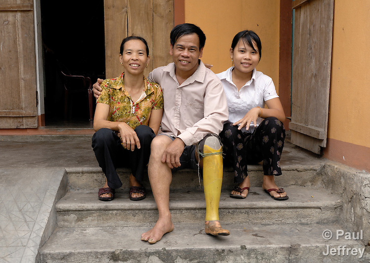 Nguyen Xuan Hien, who lost a leg to a landmine during the U.S. war against Vietnam, sits in front of his home in Bo Trach with his wife, Le Van Thoan, and his daughter, Nguyen Thi Que.