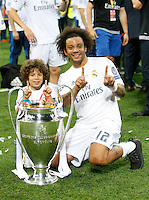 Calcio, finale di Champions League: Real Madrid vs Atletico Madrid. Stadio San Siro, Milano, 28 maggio 2016.<br /> Real Madrid&rsquo;s Marcelo and his child pose with the Champions League trophy at the end of the final match against Atletico Madrid, at Milan's San Siro stadium, 28 May 2016. Real Madrid won 5-4 on penalties after the game ended 1-1.<br /> UPDATE IMAGES PRESS/Isabella Bonotto