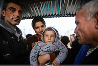 Pictured: A young boy holds his brother at the Idomeni camp Monday 29 February 2016<br /> Re: A crowd of migrants has burst through a barbed-wire fence on the FYRO Macedonia-Greece border using a steel pole as a battering ram.<br /> TV footage showed migrants pushing against the fence at Idomeni, ripping away barbed wire, as FYRO Macedonian police let off tear gas to force them away.<br /> A section of fence was smashed open with the battering ram. It is not clear how many migrants got through.<br /> Many of those trying to reach northern Europe are Syrian and Iraqi refugees.<br /> About 6,500 people are stuck on the Greek side of the border, as FYRO Macedonia is letting very few in. Many have been camping in squalid conditions for a week or more, with little food or medical help.