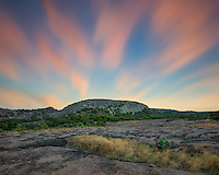 From the north side of Enchanted Rock in the Texas Hill Country, evening falls over the iconic landmark. The clouds are blurred from a long exposure in an attempt to show the fast movement of colors in the sky.