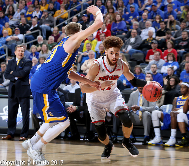 SIOUX FALLS, SD: MARCH 6: 	Trey Burch-Manning #12 from the University of South Dakota drives against Reed Tellinghuisen #23 from South Dakota State University during the Summit League Basketball Championship on March 6, 2017 at the Denny Sanford Premier Center in Sioux Falls, SD. (Photo by Dave Eggen/Inertia)