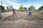 Deng Akosa, 13, and Juma Koko, 14, prepare the ground for planting in the Rhino Refugee Camp in northern Uganda. As of April 2017, the camp held almost 87,000 refugees from South Sudan, and more people were arriving daily. About 1.8 million people have fled South Sudan since civil war broke out there at the end of 2013. About 900,000 have sought refuge in Uganda. <br /> <br /> The boys' families fled from Yei, South Sudan, in 2016.