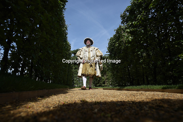 A figure dresses as King Hanry VII admires a maze garden that celebrates the 25th anniversary  of the RHS Hampton Court Flower show. <br /> <br /> Bethany Clarke / RHS / London 29.6.15