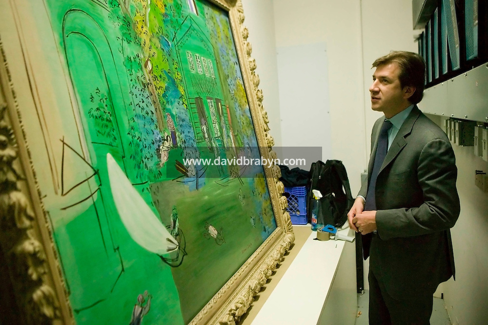 28 April 2006 - New York City, NY - Sotheby's Vice-President for Impressionism and Modern Art, David Georgiades, examines a painting by Raoul Duffy, Nogent-sur-Marne, at the Sotheby's auction house in New York City, USA, 28 April 2006. The piece, part of a major sale of impressionist and modern art, is expected to bring in between $500,000 and $700,000.