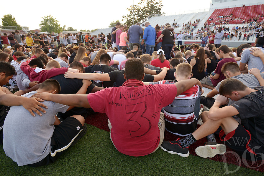Joseph Briand-Carter (center), a Springdale sophomore football player, wears a shirt decorated in memory of his teammate Kyler Williams on Sunday Sept. 25, 2016 as students surround Williams' family in support during a gathering at Jarrell Williams Bulldog Stadium in Springdale to honor Williams, a star wide receiver at Springdale who died overnight in a single vehicle crash.
