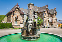 Germany, Rhineland-Palatinate, Ahr-Valley, Bad Neuenahr-Ahrweiler, district Ahrweiler: historical train-station at Landrat-Joachim-Weiler-Square with fountain Winzerbrunnen by Otto Kley | Deutschland, Rheinland-Pfalz, Ahrtal, Bad Neuenahr-Ahrweiler, Stadtteil Ahrweiler: historisches Gebaeude des Alten Bahnhofs in Ahrweiler mit Winzerbrunnen von Otto Kley am Landrat-Joachim-Weiler-Platz