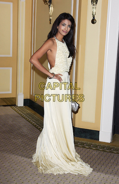 KONNIE HUQ.Ndoro Childrens Charities Gala Fundraiser at the Dorchester, Park Lane, London, England. .September 17th 2009.full length cream gold long maxi dress ruffles yellow hand on hip.CAP/ROS.©Steve Ross/Capital Pictures.