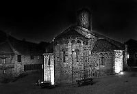 Low angle view of Santa Maria de Taull Church at night, 1123, consecrated by Ramon Guillem, the bishop of Roda, Taull, Province of Lleida, Catalonia, Spain. The church was built with three naves, each ending with an apse which cornice is decorated with Lombard arches. The square bell tower is the oldest part of the church. The church was heavily renovated in the 18th century. Santa Maria de Taull Church is part of the Catalan Romanesque churches of the Vall de Boí which were declared a World Heritage Site by UNESCO in November 2000. Picture by Manuel Cohen