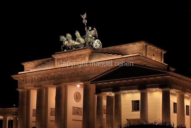 The Brandenburg Gate or Brandenburger Tor at night, 18th century, a neoclassical triumphal arch marking one of the old city gates of Berlin, at the end of Unter den Linden, Berlin, Germany. The gate was commissioned by King Frederick William II of Prussia as a sign of peace and built by Carl Gotthard Langhans 1788-91. It stood inaccessible next to the Berlin Wall during Germany's Partition and was restored 2000-02 by the Stiftung Denkmalschutz Berlin. It consists of 12 Doric columns and is topped by a statue of a quadriga, a chariot pulled by 4 horses. Picture by Manuel Cohen