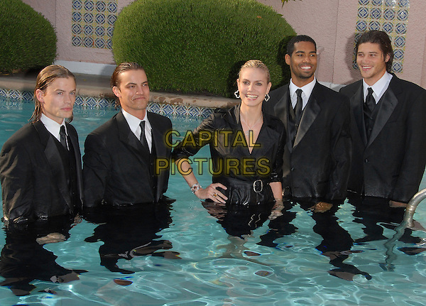 HEIDI KLUM.Falls in the swimming pool at The unveiling of her second collection of the Heidi Klum Collection for QVC in Beverly Hills, California, USA..April 6th, 2007.half length water wet black top funny hand silver necklace earrings suit hand on hip.CAP/DVS.©Debbie VanStory/Capital Pictures