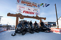The 2010 trail breakers, who run the trail from Anchorage to Nome, pose for a group photo under the burl arch finish in Nome, Alaska