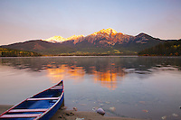Canoe at Pyramid Lake as the alpenglow of an autumn dawn kisses Pyramid Peak in Jasper  National Park