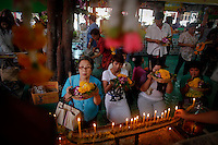 People pray in front of Red Lips shrine at Wat Prommanee temple in Nakhon Nayok province where people lay in coffins during a religious ritual May 28, 2011. Hundreds of Buddhist believers pay small fee to lay in nine pink coffins at 9:09 am and 1:09 pm every day in Wat Prommanee temple during its unusual daily resurrection service that they believe will wash away bad luck and prolong life.      REUTERS/Damir Sagolj (THAILAND)