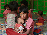 One day after they made the perilous crossing from Myanmar into Bangladesh, 9-year old Ruzi holds her sleeping 2-year old sister Jainuray in a United Nations clinic for severely malnourished Rohingya children in the Balukhali Refugee Camp near Cox's Bazar, Bangladesh. She has been feeding her Plumpy'nut, a peanut-based supplement given to malnourished children. <br /> <br /> More than 600,000 Rohingya have fled government-sanctioned violence in Myanmar for safety in Bangladesh.