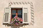 Window with green shudders and pink flowers in the small town of Viscoprano, a Swiss town in the Bregaglia Valley which dates back to 1096. The decorations on the house are patterns scratched out of the still wet wall, decorative artwork called sgraffiti, traditionally done in two colors and originating in Italy, brought to the Engadin region of Switzerland in the 16th century and is still used today