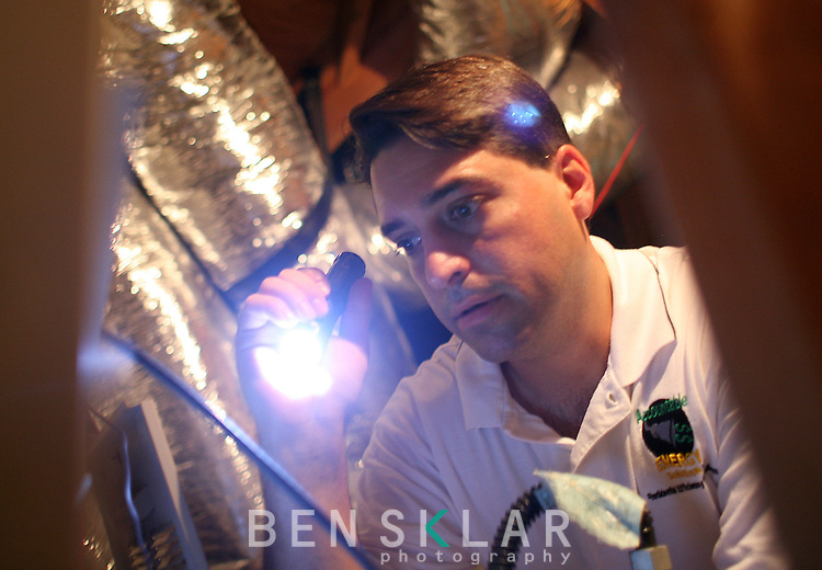 Scott Young, owner of accountable energy solutions, looks for leaks on the air conditioning unit blower door at a home in the Steiner Ranch subdivision on Monday, June 15, 2009 in Austin, Texas. Young, a third party contractor, also checks insulation and looks for weak areas where the energy efficiency could be improved to meet code requirements as a part of Austin Energy's Energy Conservation Audit and Disclosure Ordinance for homes transferring ownership...