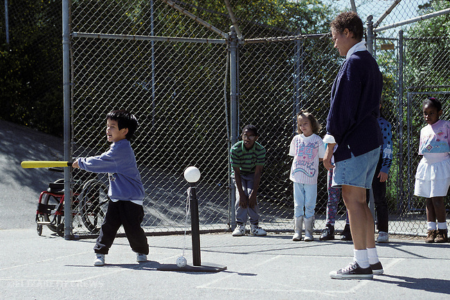 "Oakland, CA Adaptive P.E. teacher supervising learning handicapped students with ""T"" ball play"