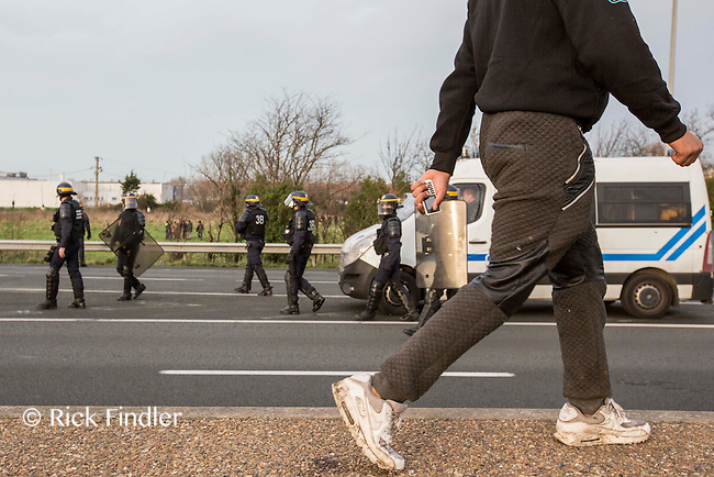 FRANCE, Calais: 17 December 2015 A refugee walks in front of riot police outside of the Euro Tunnel entrance in Calais this afternoon. Hundreds of refugees walked hours through Calais today to reach the Euro Tunnel from 'The Jungle' camp to try and get to England. Rick Findler  / Story